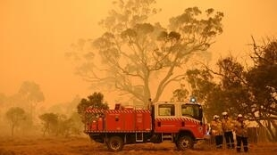 Les pompiers protègent une propriété contre les feux de brousse qui brûlent près de la ville de Bumbalong, au sud de Canberra, le 1er février 2020.
