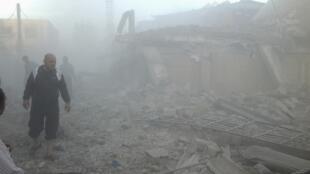 Habitantes de Erbeen, ao sul de Damasco, procuram por vítimas após bomberdeio do exército.