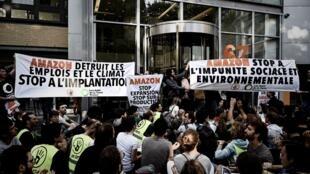 """Biểu ngữ tố cáo  tập Amazon """"phá hoại công việc làm và khí hậu"""", kêu gọi  """"Amazon chấm dứt phát triển, chấm dứt sản xuất dư thừa"""". Ảnh ngày 2/07/2019, ở Clichy, Paris."""