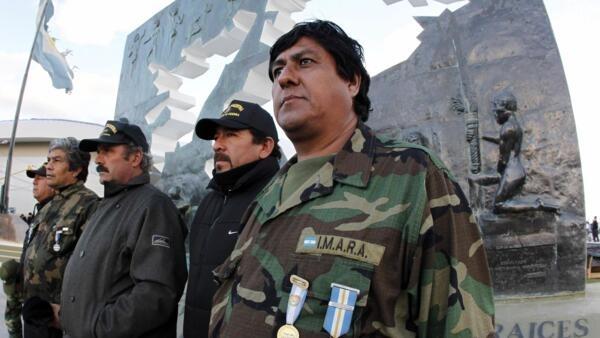 Veteranos argentinos posam em frente a monumento em homenagem à Guerra das Malvinas, em Ushuaia.