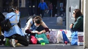 Une femme sans-abri reçoit l'aide d'une association d'aide aux sans domicile fixe à Montpellier, le 18 mars 2020.