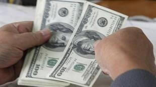 Một khách hàng đang đếm số đô la Mỹ vừa lãnh được từ một ngân hàng ở Hà Nội. Ảnh chụp ngày 29/11/2010.