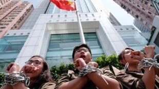 Thanh niên Hồng Kông, xiềng tay vào nhau, biểu tình trước một trụ sở Trung Quốc ở Hồng Kông, ngày 8/6/2019.
