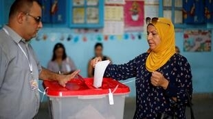 A woman casts her vote in a polling station during presidential election in Tunis, Tunisia, September 15, 2019.