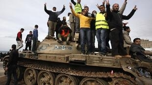 Anti-government protesters on an army tank near a square where people are protesting in Benghazi, 23 February 2011