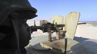 A peacekeeper from the Amisom mans a weapon atop an armoured personnel carrier