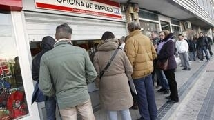 People wait for the opening of a government employment office in Madrid, Spain