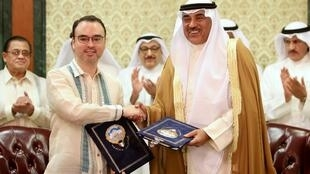 Le secrétaire philippin des Affaires étrangères Alan Peter Cayetano et son homologue koweïtien Cheikh Sabah al-Khaled al-Sabah après la signature de l'accord réglementant le travail des domestiques, à Koweït, le 11 mai 2018.