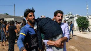 Des centaines d'habitants de la province d'Idleb au nord-est de la Syrie manifestent le 30 août 2019, près de la ville d'Atme où les forces turques ont répliqué avec des gaz lacrymogènes.
