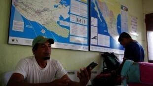 Deux migrants honduriens profitent d'un moment de repos pour recharger leur téléphone à Esquipulas au Guatemala. Le 10 avril 2019.