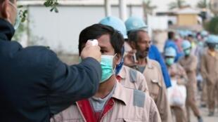 Contrôle de la température des ouvriers sur un chantier à Ahmadi, au Koweït, le 28 mars 2020.
