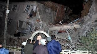 People outside a collapsed building after a 6.8 earthquake struck Elazig city centre in the eastern Turkey, Friday,  24 January, 2020.