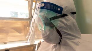 Un sanitario muestra el 11 de marzo de 2020 un equipo de protección en el marco de los preparativos en el Hospital de Enfermedades Infecciosas Wilkins de Harare para tratar posibles casos de coronavirus COVID-19