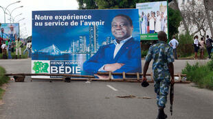 A soldier passes a billboard of presidential candidate Henri Konan Bedie