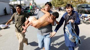 Homem carrega um garoto ferido para o hospital.