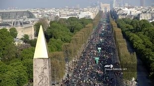 Runners run on the Champs Elysees in Paris as they take part in Paris Marathon on April 14, 2019.