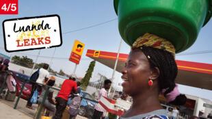 Une vendeuse de rue passe devant une station-service de la Sonangol, à Luanda, en Angola, en novembre 2018.