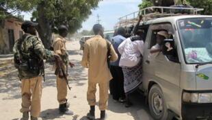 Somali soldiers check a minibus taxi in Mogadishu