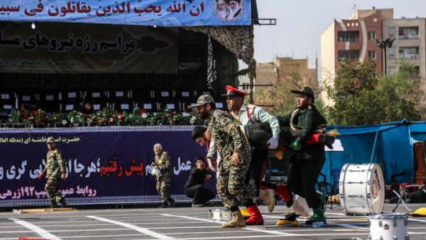 Soldados iranianos transportam camarada ferido em atentado durante comemoração da Guerra Irã-Iraque (1980-1988).