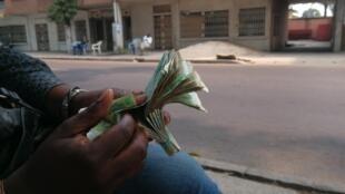 Un changeur de monnaie manipule des billets de francs CFA sous les manguiers de l'allée du Beach, à Brazzaville.