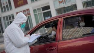 北京街头防疫人员向路人进行调查。