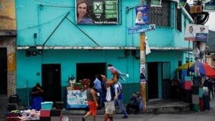 Une famille guatémaltèque passe devant des affiches de la campagne présidentielle à Chinautla, dans la banlieue de Guatemala City, le 9 août 2019.