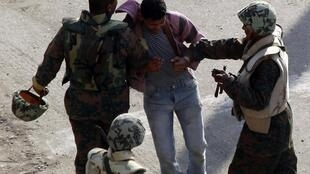 An Egyptian army member arrests a protester during clashes in Tahrir Square, Cairo on 2 February 2011