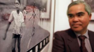 Le photographe Nick Ut pose à côté de la photo qui lui a valu une notoriété mondiale : la petite fille au napalm ou l'horreur de la guerre.