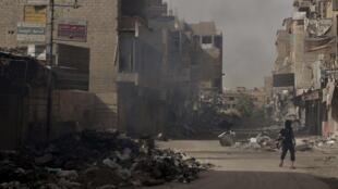 Rebelde sírio nas ruas destruidas de Deir al-Zor.