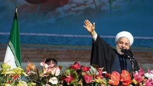 The Iranian President Hassan Rohani waves during a rally in Tehran marking the 35th anniversary of the Islamic revolution, 11 February, 2014