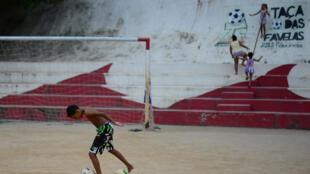 Menino joga futebol na favela Cidade de Deus, no Rio.