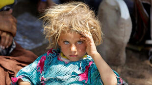 A girl from the minority Yazidi sect, fleeing the violence in the Iraqi town of Sinjar, rests at the Iraqi-Syrian border crossing in Fishkhabour, Dohuk province August 13, 2014.