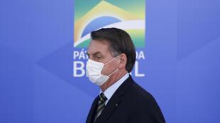 El presidente brasileño Jair Bolsonaro llega a una conferencia de prensa con una máscara facial de protección a causa de la pandemia del coronavirus, el 18 de marzo de 2020