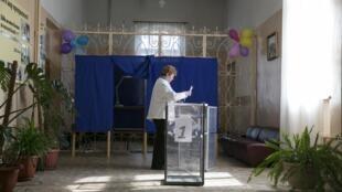 Mulher prepara urna de votação para referendo na Crimeia.
