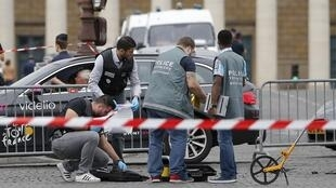 French police look for evidence after the security cordon, installed for the arrival of the Tour de France, was violated.