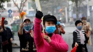 Người dân tập thể dục buổi sáng bên hồ Hoàn Kiếm, Hà Nội, đeo khẩu trang đề phòng lây nhiễm virus corona, Hà Nội, ngày 03/02/2020.