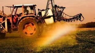 Un agriculteur traite son champ avec des pesticides.