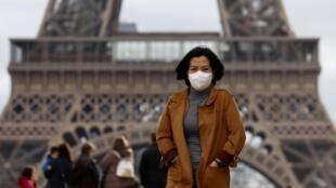 Turista asiática usa máscara de proteção ao visitar a Torre Eiffel, em Paris.