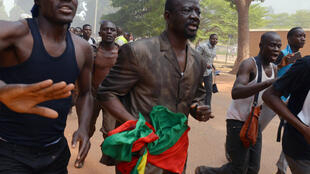 An MP flees the parliament in Ouagadougou as demonstrators occupy it on Thursday