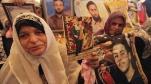Mulheres palestinas carregam fotos de seus filhos detidos em prisões israelenses, durante manifestação na sede da  Cruz Vermelha, em Gaza, nesta segunda-feira.