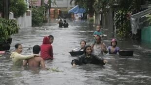 Residents wade through floodwaters in Tinajeros, Malabon city, Metro Manila 7 August 2012.