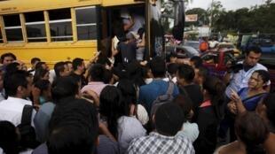 """Salvadoreños intentan subir a un bus del gobierno durante el paro de transporte decretado por las pandillas o """"maras""""."""