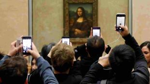 資料圖片:遊客在巴黎盧浮宮《蒙娜麗莎》展廳競相拍照。攝於2018年12月