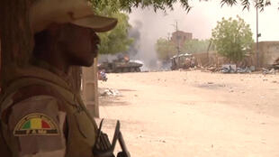 A still image taken from a video shows a Malian armed forces (FAMa) soldier standing guard as smoke and flames are pictured in the distance after a car bomb attack in Gao, northern Mali July 1, 2018.