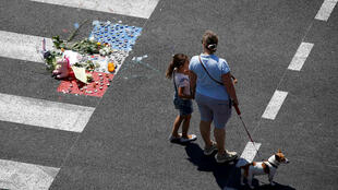 A woman and a child stand near a makeshift memorial to pay tribute to victims of the truck attack along the Promenade des Anglais in Nice