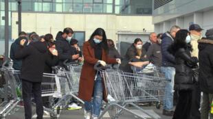 Des Italiens portent des masques de protections à l'entrée d'un supermarché fermé de Casalpusterlengo, une des villes placées à l'isolement, le 23 février 2020.