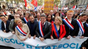 """Ícones da esquerda francesa, Jean-Luc Mélenchon (ao centro) e Benoit Hamon (à sua esquerda) durante protestos deste sábado, 23 de setembro de 2017, contra a reforma da lei trabalhista, em Paris. Nas mãos, a faixa com os dizeres """"Golpe de Estado social""""."""