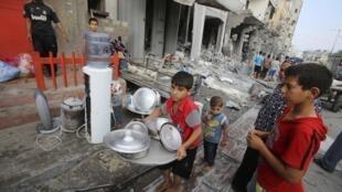 Crianças palestinas retiram o que sobra de suas casas destruídas por um bombardeio,no dia 26 de agosto.