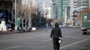 Un homme marche le long de la rue Financial, dans le centre de Pékin, en Chine, alors que le pays est frappé par l'épidémie de coronavirus, le 3 février 2020.