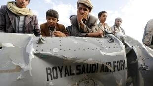 People stand by part of a Saudi fighter jet found in Bani Harith district north of Yemen's capital Sanaa, May 24, 2015.